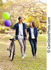 cute teenage couple with bicycle outdoors