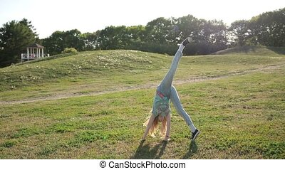 Cute teenage girl doing cartwheel at green meadow