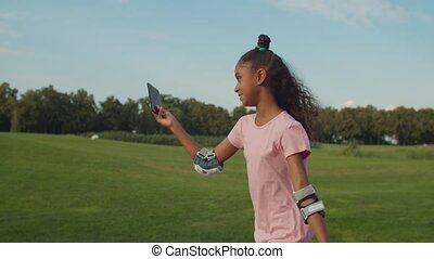 Side view of attractive mixed race teenage girl with trendy haircut roller blading in summer park, broadcasting video online for vlog using cellphone and sharing with audience about roller skating.