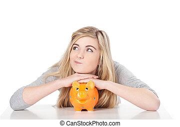 Cute teenage girl posing with piggy bank
