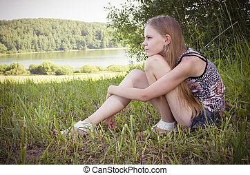 cute teenage girl sitting on the grass