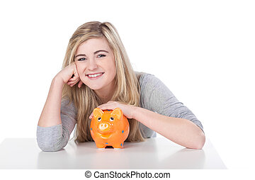 Cute teenage girl smiling while holding piggy bank - Image...