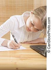 Cute Teenage Girl Writing Her Homework t the Table