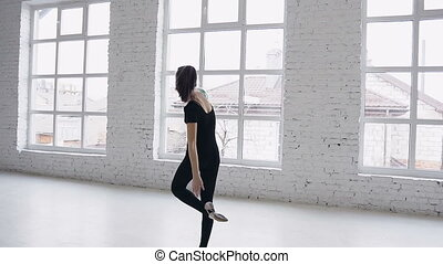 Cute teenage gymnast makes training with ball on a white background near big windows at gymnastics school. Sporting exercise, stretch, flexibility, aerobics