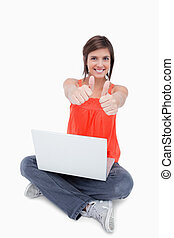 Cute teenage sitting cross-legged and showing her happiness with thumbs up