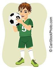 Cute teenager boy holding soccer ball