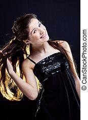 teenager girl showing beautiful healthy long dark hair on...