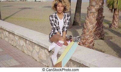 Cute teenager sitting on ledge with skateboard - Cute...
