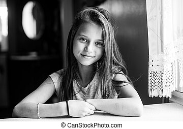 Cute ten-year-old girl posing for the camera sitting at the table. Black and white photography.