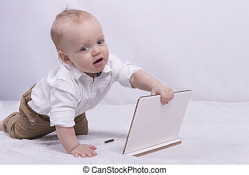 Cute thoughtful boy in white shirt playing with a tablet. Funny infant boy with laptop looks like little businessman