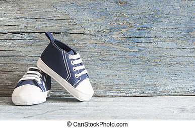 Cute tiny baby shoes on a wood with copy space for your text