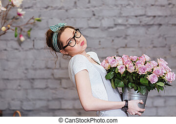 Cute tired young woman holding heavy bucket with pink roses