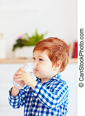 cute toddler baby boy drinking fresh water from glass early in the morning in pajamas