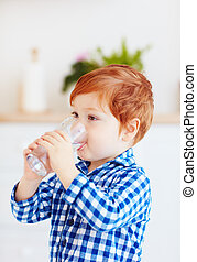 cute toddler baby boy drinking fresh water from glass early in the morning