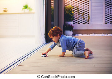 cute toddler baby boy playing with toy car at the patio with open space kitchen and sliding doors
