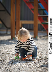 Cute toddler baby girl playing with shovel at playground