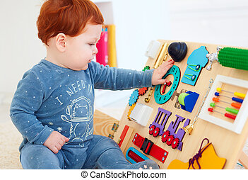 cute toddler baby playing with busy board at home