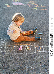 Cute toddler boy drawing with chalk on a nice day outdoors