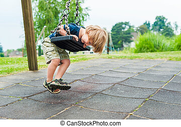 Cute toddler boy playing on playground