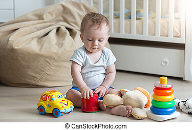 Cute toddler boy playing with colorful toys on floor at living room