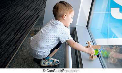 Cute toddler boy playing with toy cars and airplane in airport