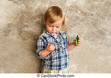 Cute toddler boy playing with toy cars outdoors