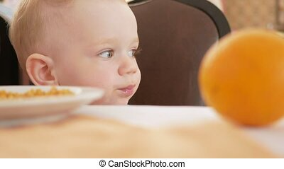 Cute toddler boy sitting in cafe and waiting for food. He reviews the visitors around