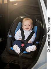 Cute toddler boy sitting in child seat at car