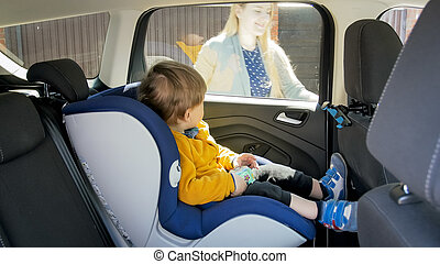 Cute toddler boy sitting in safety car seat
