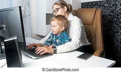 Cute toddler boy sitting on mothers lap working in office