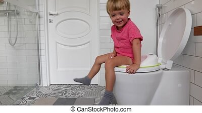Cute toddler boy sitting on toilet in bathroom at home
