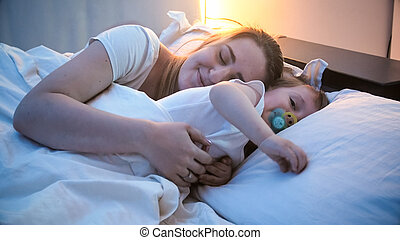 Cute toddler boy sleeping with mother in bed at night
