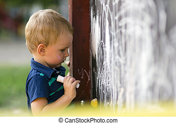 Cute toddler drawing with chalk outdoors