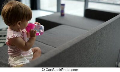 Cute toddler drinking water on the sofa