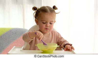 Cute toddler eating cereals for breakfast - Adorable little ...