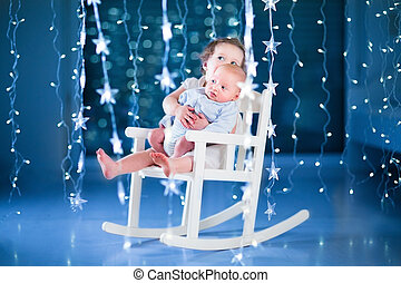 Cute toddler girl and her newborn baby brother relaxing together