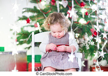 Cute toddler girl eating candy under a beautiful Christmas tree