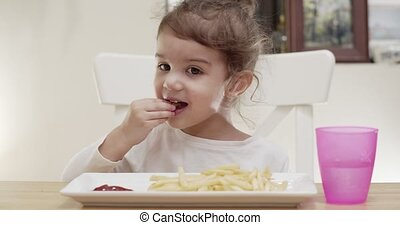 Cute toddler girl eating french fries. Cinematic 4K footage.