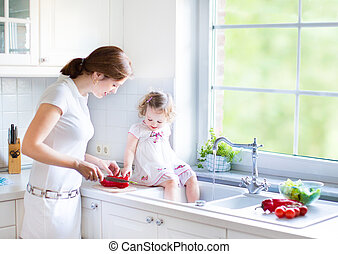 Cute toddler girl helping her mother to cook vegetables in a bea