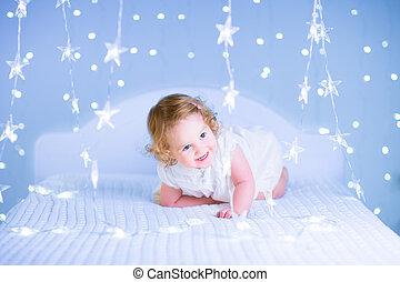 Cute toddler girl in a bedroom