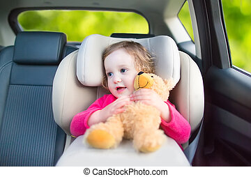 Cute curly laughing and talking toddler girl playing with a toy bear enjoying a family vacation car ride in a modern safe vehicle sitting in a baby seat with belt having fun watching out of the window