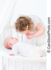 Cute toddler girl in a white dress kissing the hand of her baby
