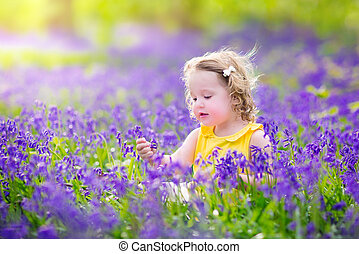 Cute toddler girl in bluebell flowers in spring - Adorable...