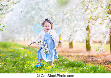 Cute toddler girl in fairy costume playing in a blooming garden