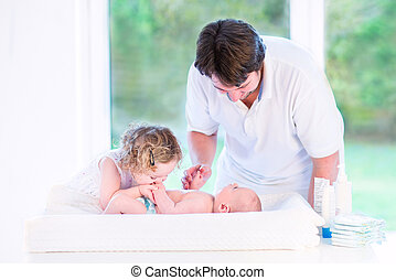 Cute toddler girl kissing her newborn baby brother on a white ch