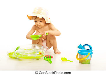 Cute toddler girl play with beach toys