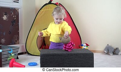 Cute toddler girl play with toy cat and climb on soft pouffe at home.