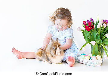 Cute toddler girl playig with a bunny on Easter next to a basket