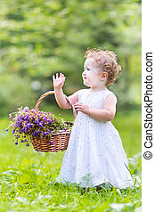 Cute toddler girl playing in the garden with a flower basket