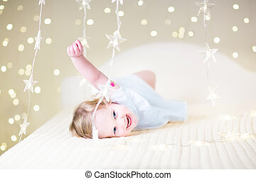 Cute toddler girl playing on a bed between warm soft Christmas l